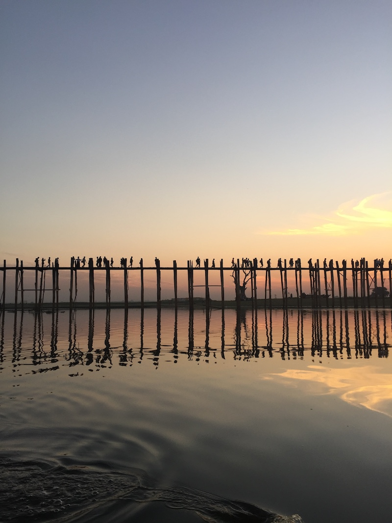 Silhouette of Ubein Bridge at sunset from the water.