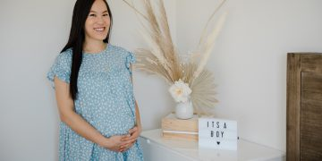 wearing blue maternity dress from pink blush with it's a boy gender reveal sign