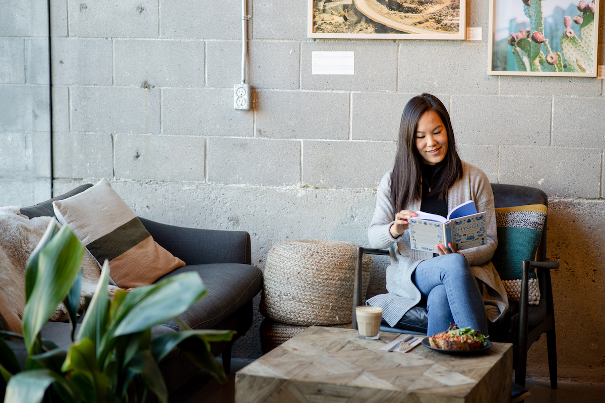 Girl Reading The Little Book of Hygge: Danish Secrets to Happy Living at a cafe