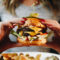 women's hands holding White Spot Burger